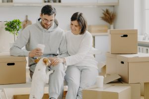Positive young husband and wife play with dog, sit on cardboard boxes, drink takeaway coffee, have break during moving day and unpacking things, wear casual outfit, enjoy living in new flat.