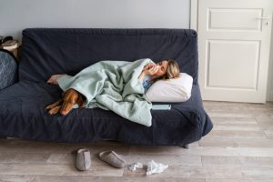 Sick woman at home lying in bed with her Vizsla dog, suffering from allergy, flu symptom, fever